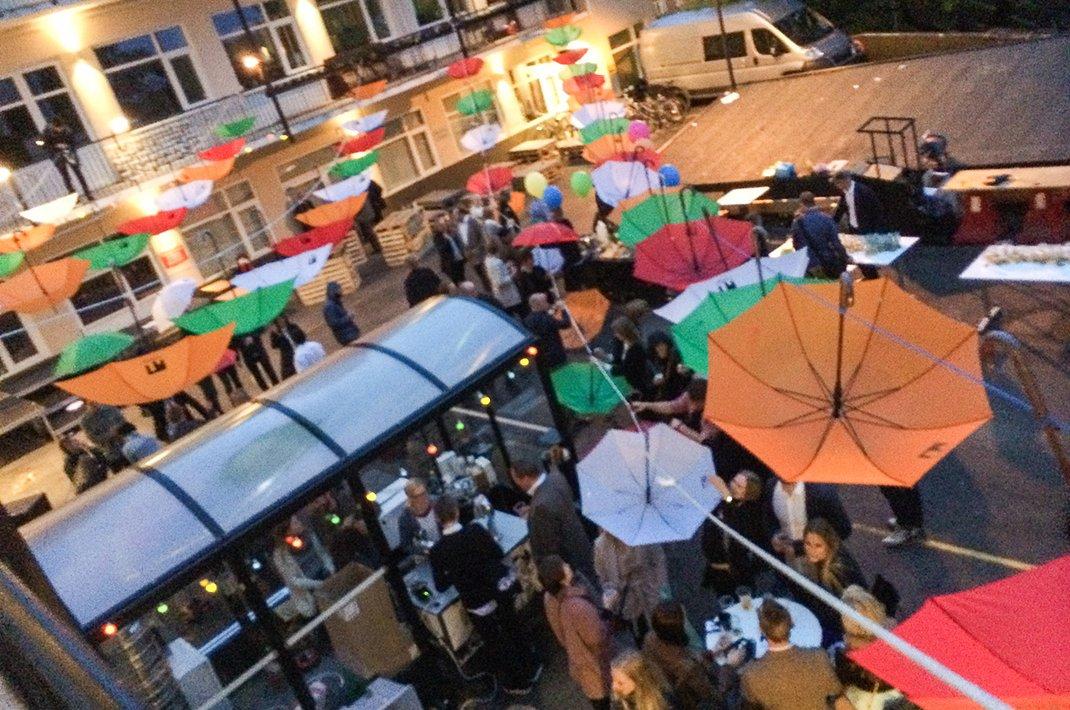 De dekorative paraplyene senkes ned slik at folk får beskyttet seg mot regnværet på kvelden