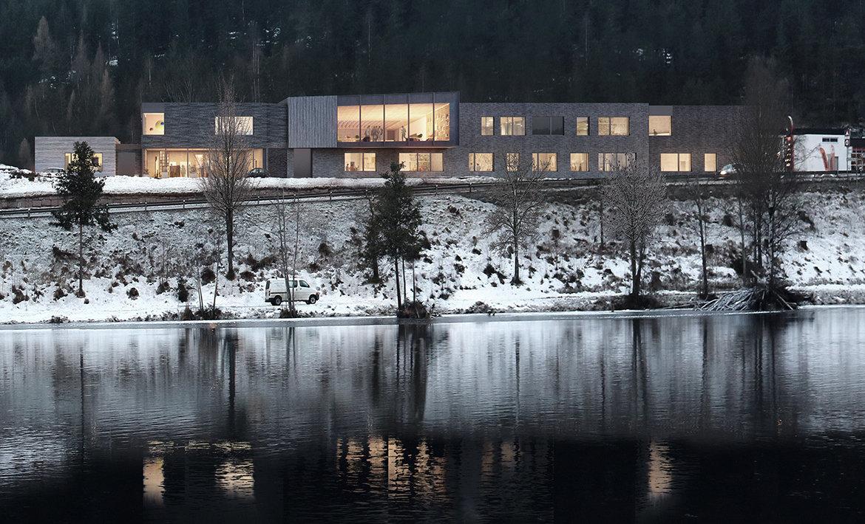 Utvendig rendering av skolen, sett fra elva. Fasade i tegl.