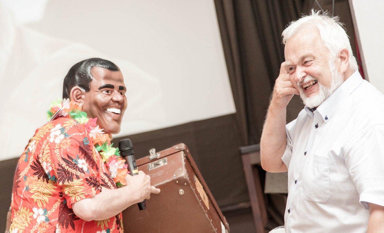 En mann utkledd som Obama med Hawaiiskjorte og koffert, og en annen mann ved siden