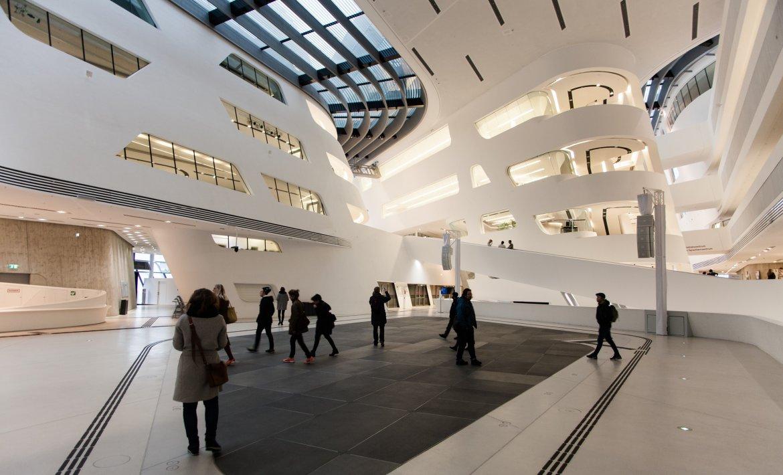 Interiørfoto av stor velkomsthall i universitetsbygg i Wien. Hvitt organisk interiør med lass i tak