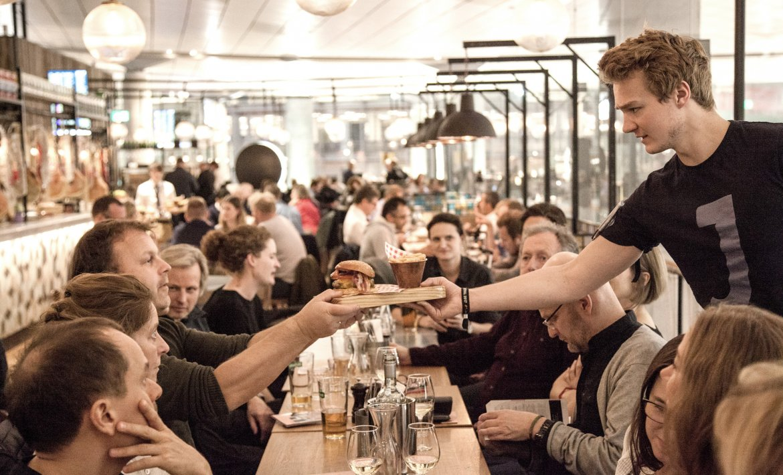 Mennesker rundt et langbord på restaurant