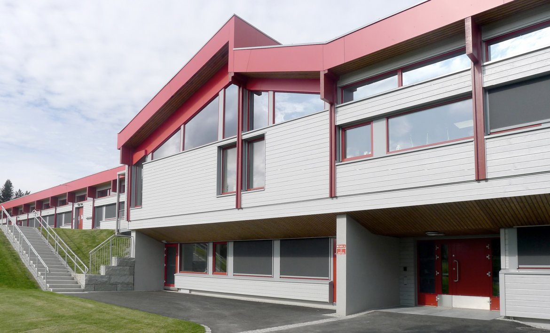 Lys trebygning med inntrukket underetasje, og kraftig rød gesims og vindusomramming