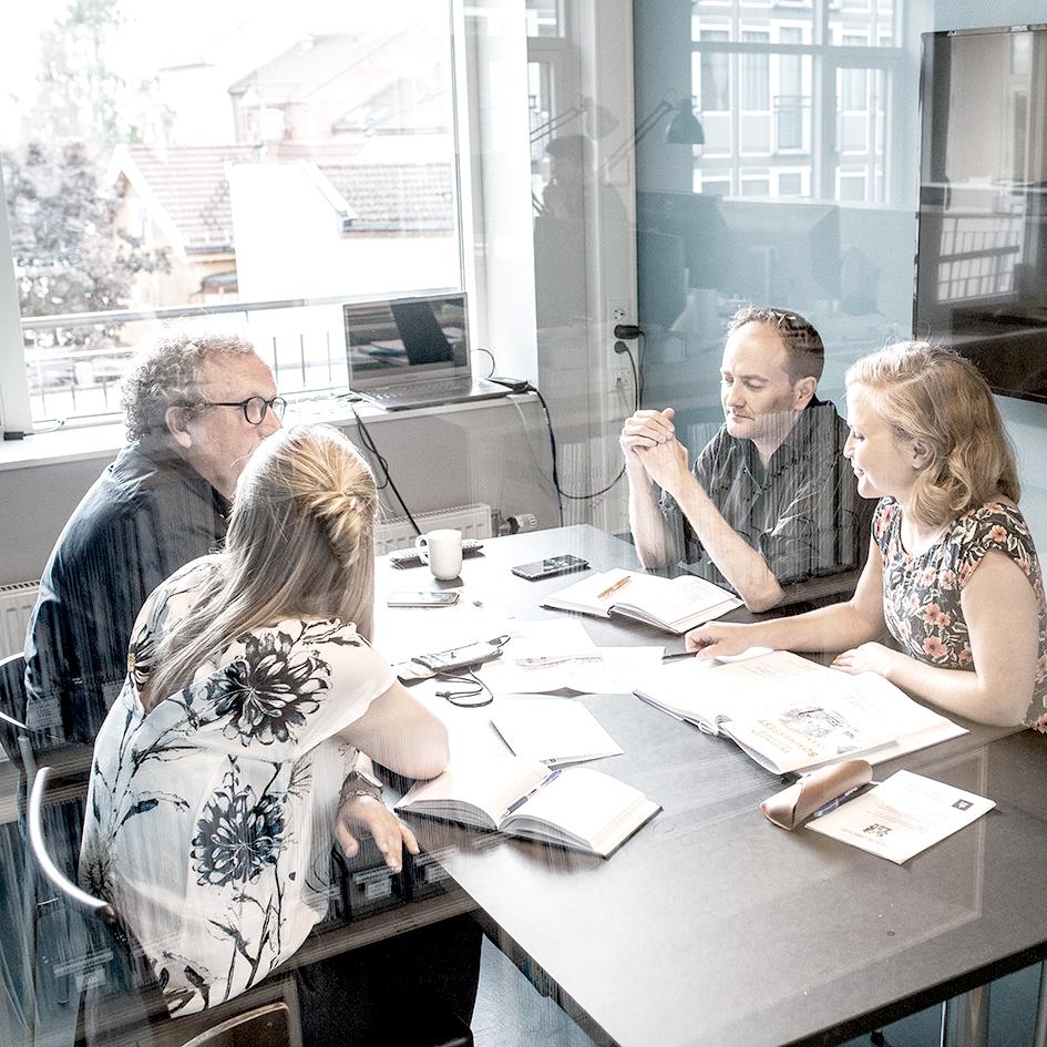 En gruppe sitter og diskuterer inne på et møterom på Enerhaugen Arkitektkontor