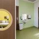 Bråtenalléen barnehage - Interiørfoto av stellerom sett gjennom koøye i dør. Interiørfoto av avdeling med grønt gulvbelegg og grønn vegg.