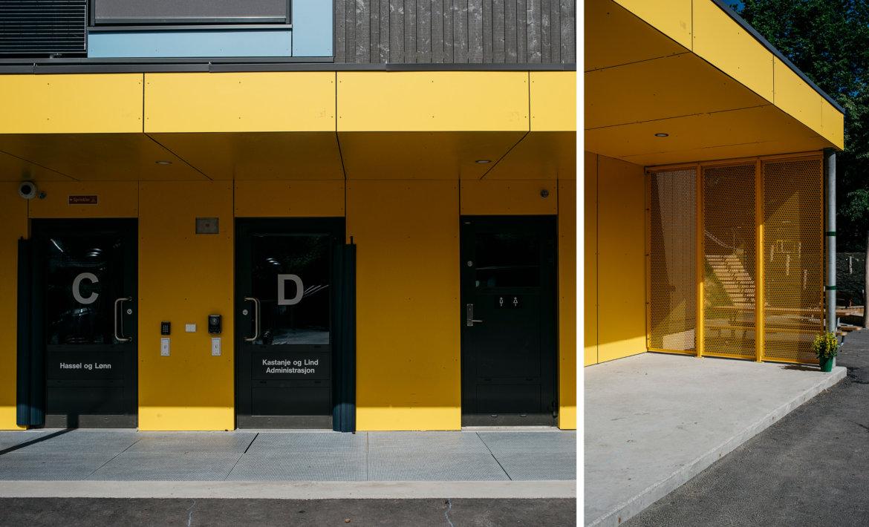 Bråtenalléen barnehage - Eksteriørfoto av adkomsdører. Gule fasadeplater på vegg og i tak over inngang.